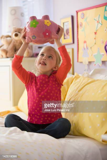 Caucasian girl shaking piggy bank