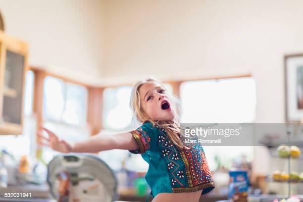 Caucasian girl singing indoors