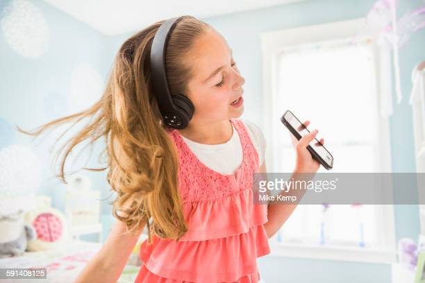Caucasian girl singing to wireless headphones
