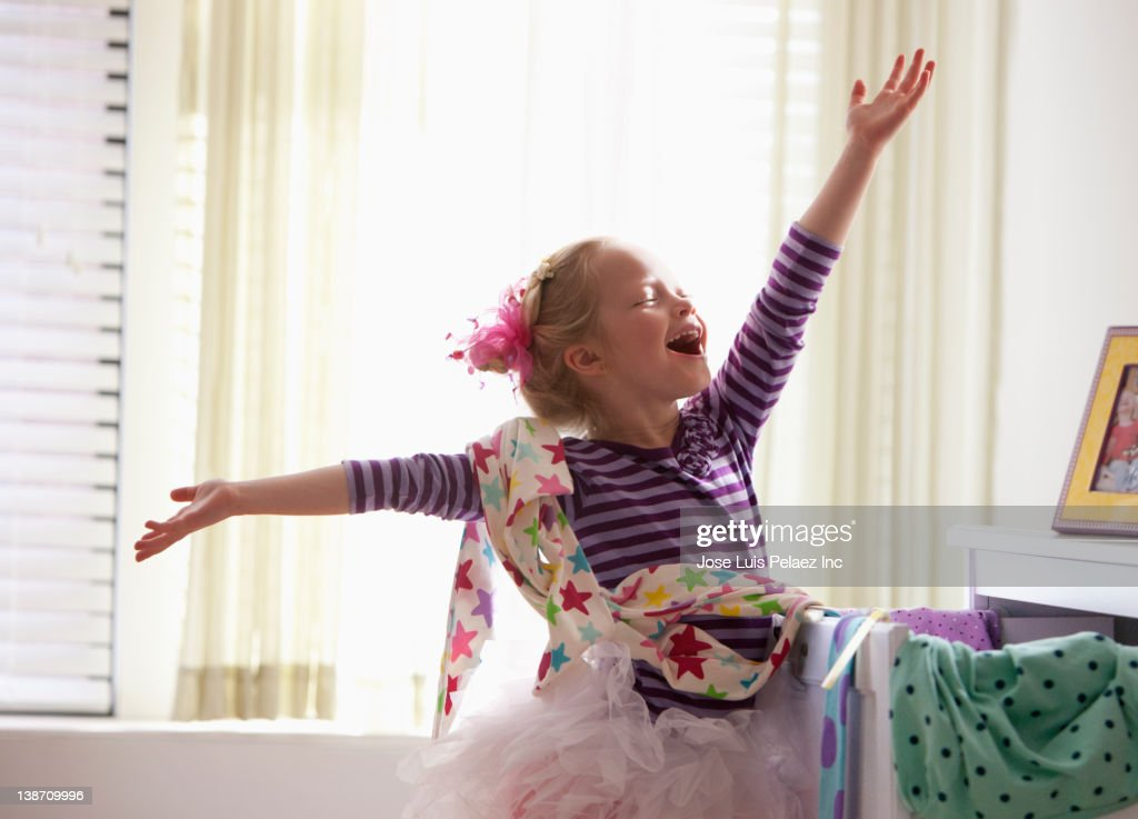 Caucasian girl singing with arms outstretched
