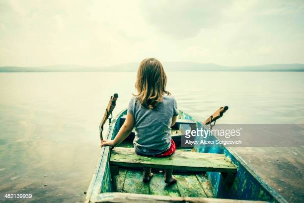 Caucasian girl sitting in boat on still lake