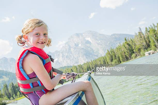 Caucasian girl sitting in canoe on lake