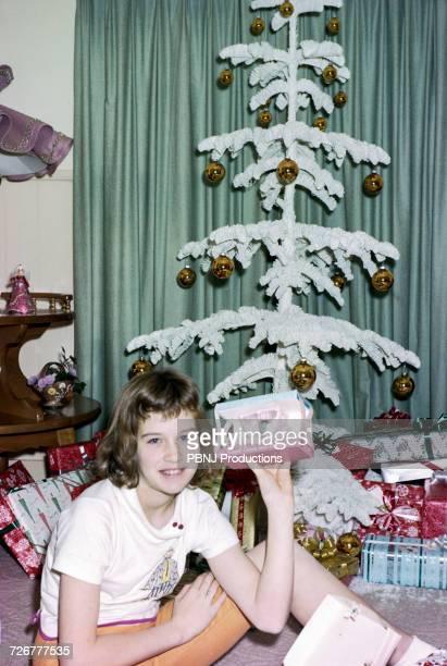 Caucasian girl sitting on floor showing Christmas gift