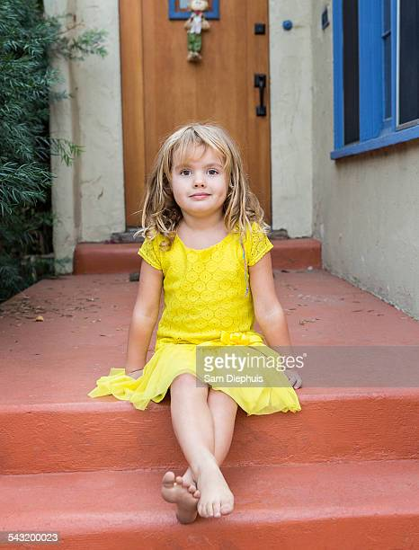 Caucasian girl sitting on front stoop