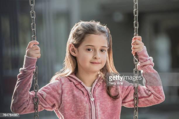 Caucasian girl sitting on swing