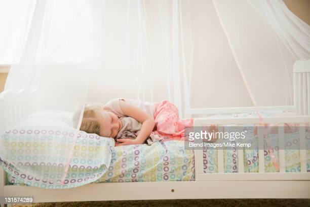 Caucasian girl sleeping in bed