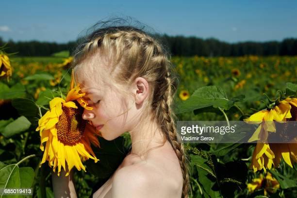 Caucasian girl smelling sunflower