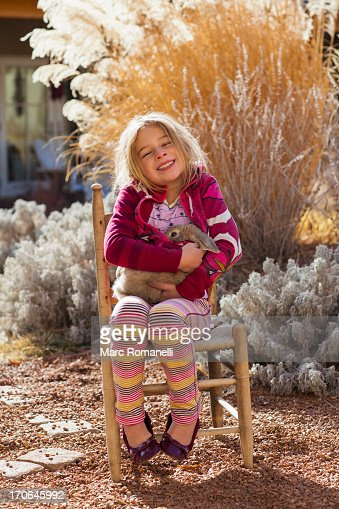 Caucasian girl smiling in chair outdoors : Stock Photo