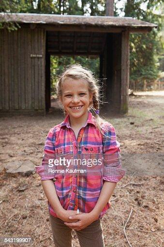 Caucasian girl smiling near barn