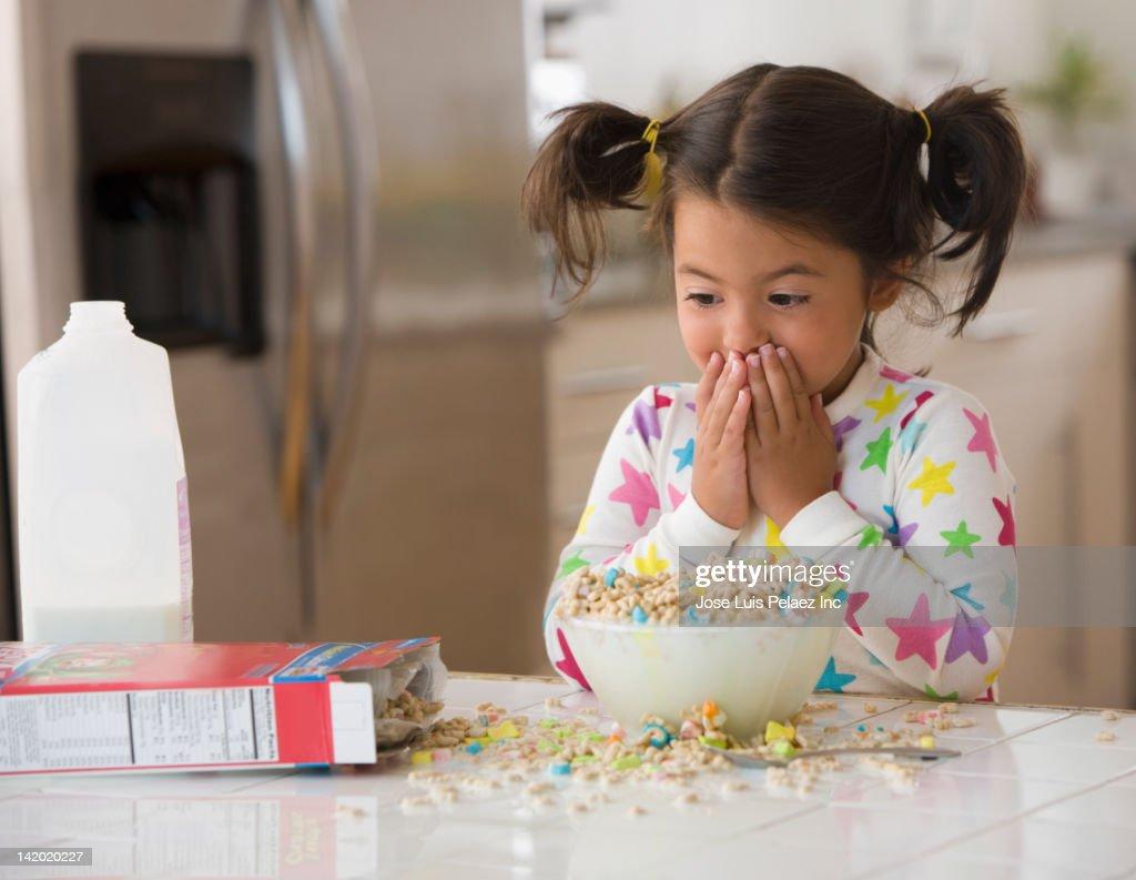 Caucasian girl spilling cereal
