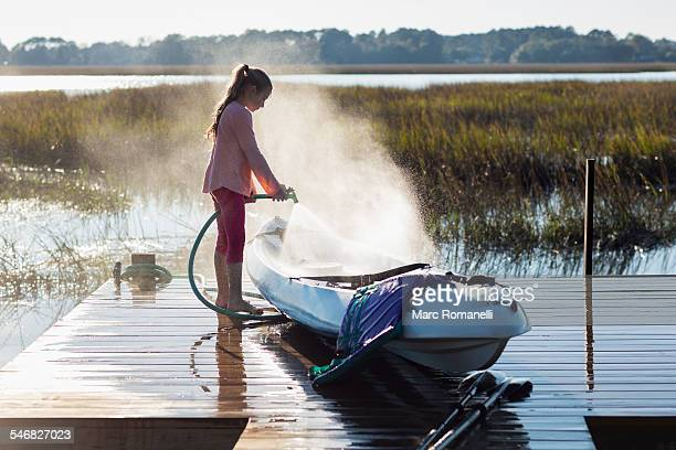 Caucasian girl spraying canoe on wooden dock over lake