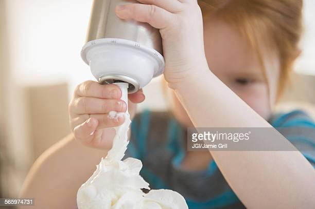 Caucasian girl spraying whipped cream