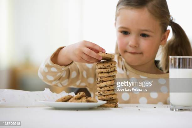 Caucasian girl stacking cookies