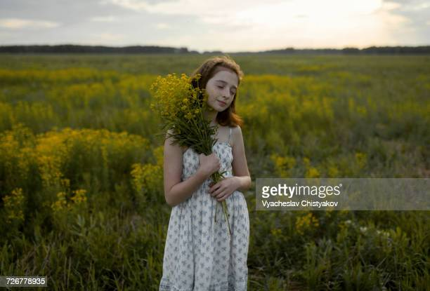 Caucasian girl standing in field holding bouquet of wildflowers