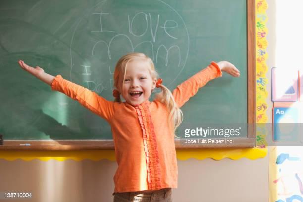 Caucasian girl standing near sign on blackboard reading I Love Mom