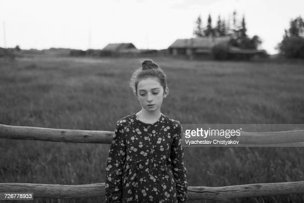 Caucasian girl standing near wooden fence
