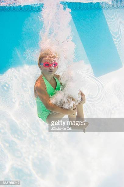 Caucasian girl swimming underwater in pool