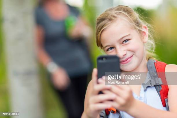 Caucasian girl taking cell phone photograph in forest