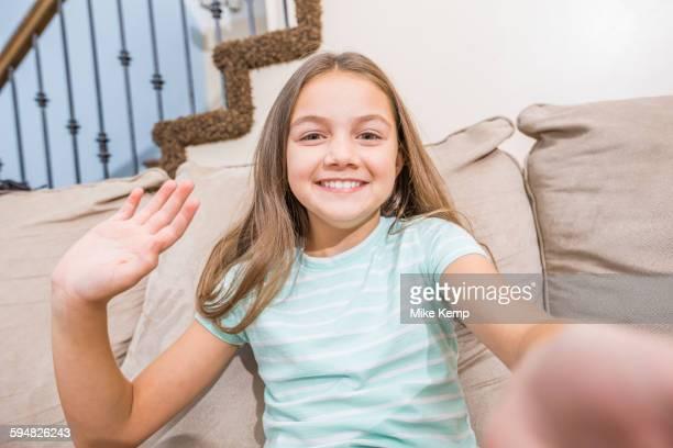 Caucasian girl taking selfie on sofa