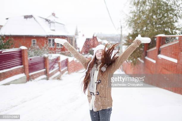 Caucasian girl throwing snow outdoors