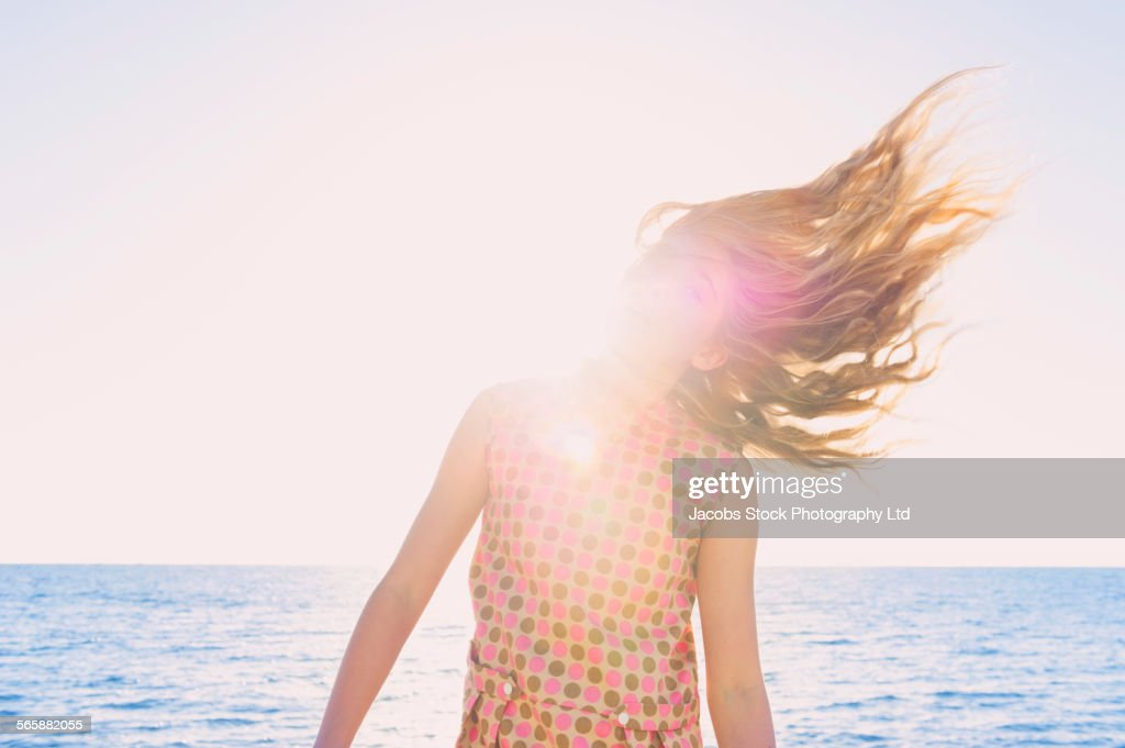 Caucasian girl tossing her hair on windy beach