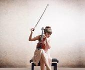 Caucasian girl tuning violin on bench
