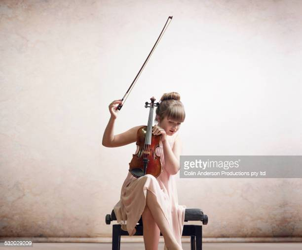 Caucasian girl tuning violin on bench