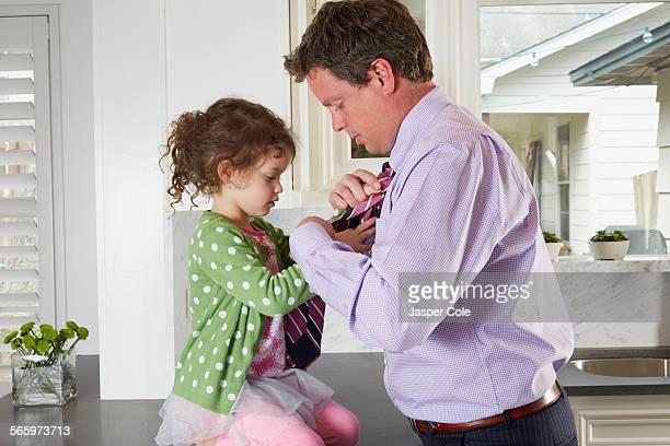 Caucasian girl tying necktie of father in kitchen