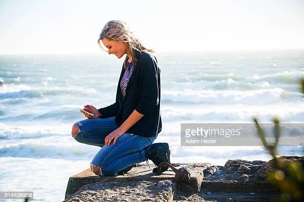 Caucasian girl using cell phone on hilltop overlooking ocean