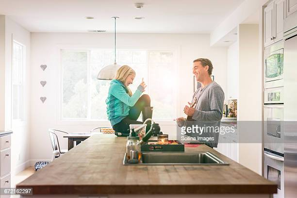 Caucasian girl using cell phone recording father playing guitar