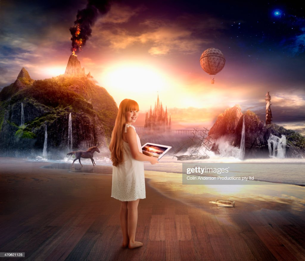 Caucasian girl using digital tablet in dramatic landscape