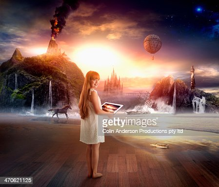Caucasian girl using digital tablet in dramatic landscape