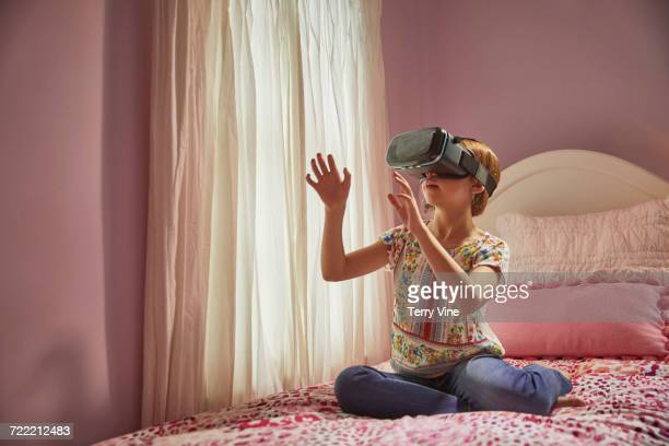 Caucasian girl using virtual reality goggles in bedroom