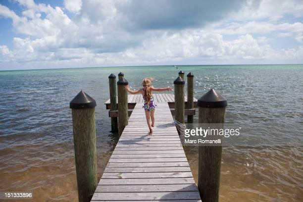 Caucasian girl walking on pier