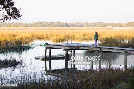 Caucasian girl walking on wooden dock in lake