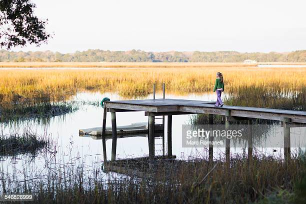 Caucasian girl walking on wooden dock in lake