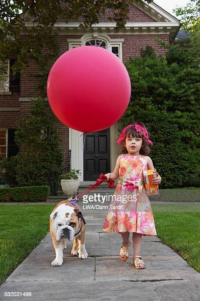 Caucasian girl walking pet dog with balloon