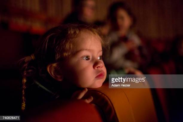 Caucasian girl watching movie in theater