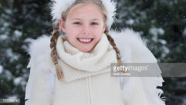 Caucasian girl wearing angel costume in winter