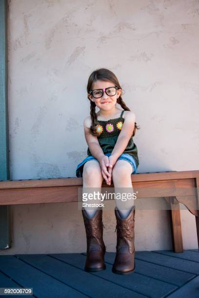 Caucasian girl wearing eyeglasses and cowboy boots on bench