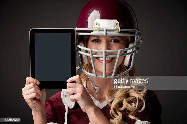 Personne de race blanche fille portant équipement de football en tenant une tablette numérique