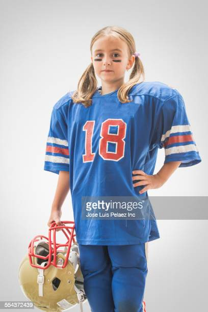 Caucasian girl wearing football jersey and helmet