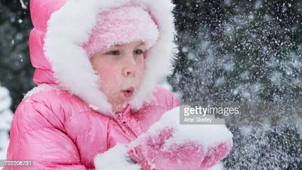 Caucasian girl wearing pink coat blowing snow