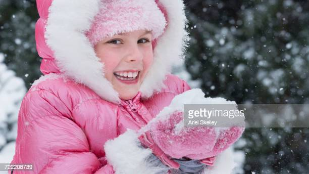 Caucasian girl wearing pink coat holding snow