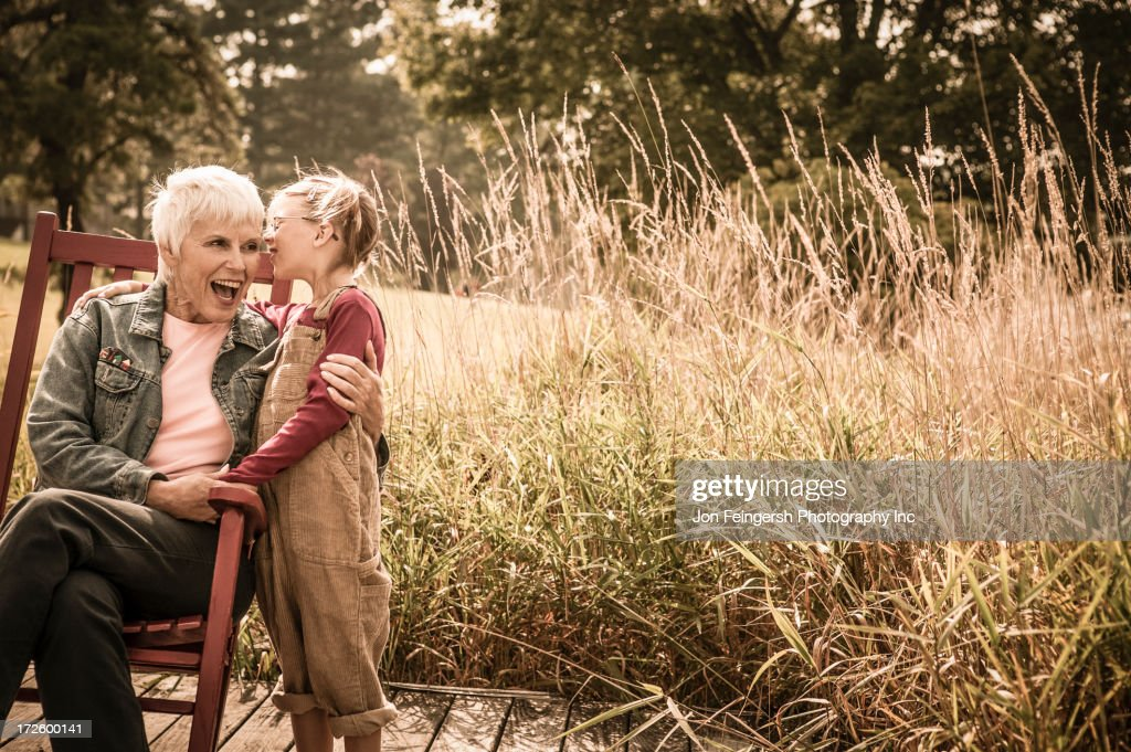 Caucasian girl whispering to grandmother outdoors : Stock Photo