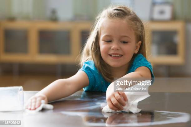 Caucasian girl wiping up spilled milk