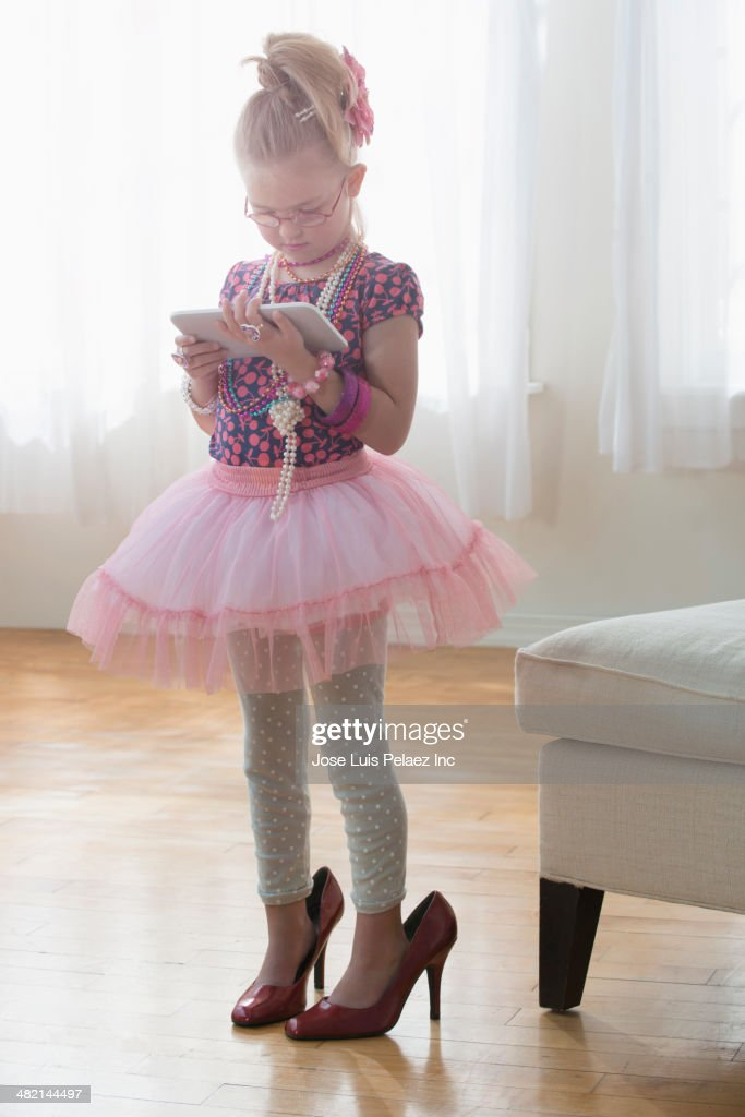 Caucasian girl with digital tablet dressed up in tutu and high heels