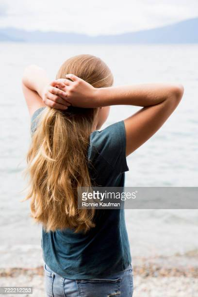 Caucasian girl with hands in hair at lake
