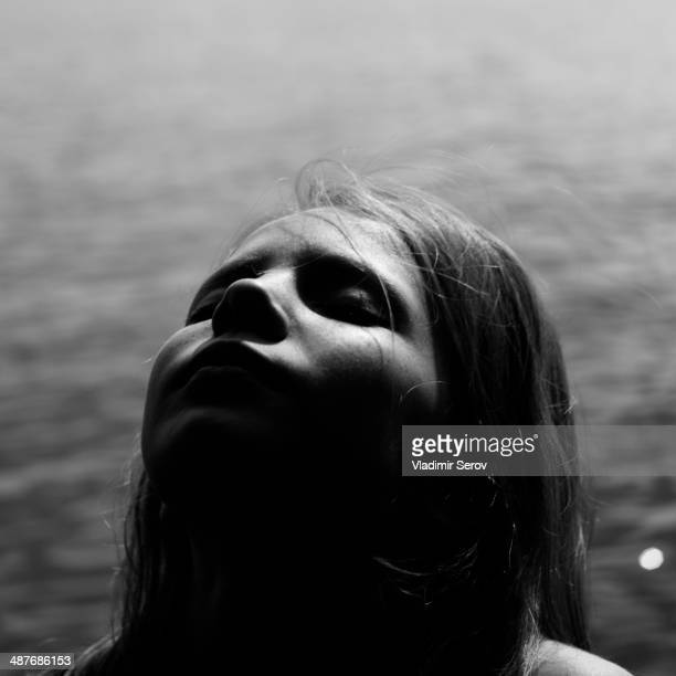 Caucasian girl with head back by lake