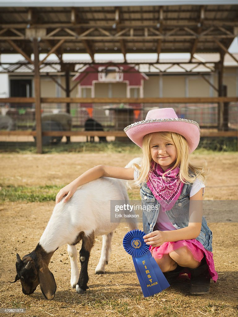 Caucasian girl with prize winning goat on farm